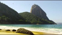Slow motion shot of the beautiful Red Beach in Rio with waves washing over exposed boulders.
