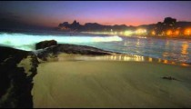 Slow motion, tracking shot of the waves crashing during a night surf at Ipanema beach