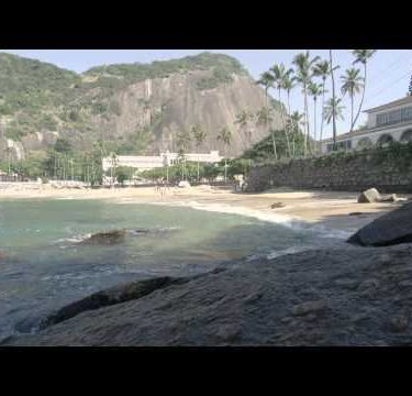 Tracking slow motion shot of surf washing on rocks with exclusive buildings and palm trees beyond.