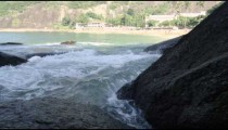 Tracking slow motion shot of heavy surf pounding on craggy rocks with building beyond.