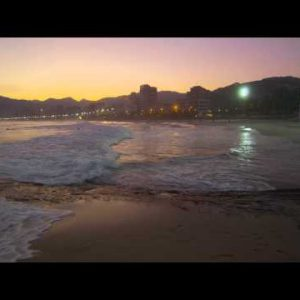 Slow motion pan of the tide coming in on Arpoador beach at sunset