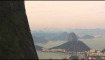Tracking shot of Rio de Janeiro's cityscape and harbor to Christ the Redeemer above.