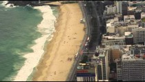 An aerial view of a beach in Rio de Janeiro with tall buildings.