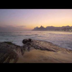 Slow motion, tracking shot of a surfer climbing rocks on Ipanema beach
