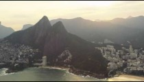 A view from a helicopter of Rio's Sugarloaf Mountain in golden sunlight.