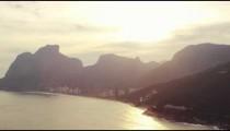 An aerial view of golden light beyond mountains in Rio de Janeiro.