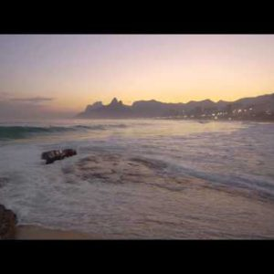 Waves rolling into Copacabana Beach as a woman walks in frame