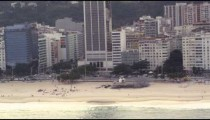 A helicopter view of Rio de Janeiro's peopled beaches and tall buildings with mountains beyond.