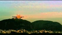 Panning shot of hills of Rio de Janeiro and landing plane