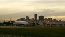 Plane taxis on runway with buildings of Rio de Janeiro in background