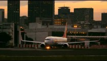 Static shot of plane taxiing down runway with Rio de Janeiro in the Background