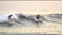 Close shot of bodyboarders and surfers offshore from Rio de Janeiro's coast.