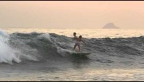 Slow motion, pan shot of surfer riding wave