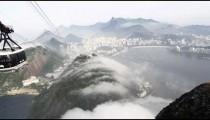 Pan of a gondola ride on a misty day over the Brazilian coastline in Rio de Janeiro, Brazil