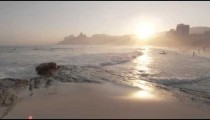 Slow motion, sunset shot of white waves rolling onto beach as people swim