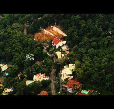 Tracking aerial view of favelas and trees on Corcovado Mountain