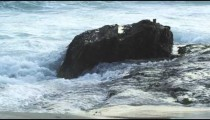 Waves hitting beach rock in slow motion