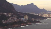 Aerial pan shot of favelas on the mountain and the city of Rio de Janeiro, Brazil