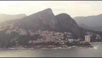 Aerial pan shot of favelas on the mountain and the city of Rio de Janeiro, Brazil with lens flare
