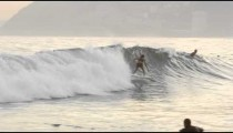 Slow motion pan shot of surfer, with large buildings and mountains in background