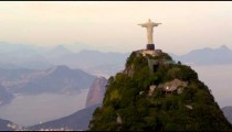 Aerial tracking footage of Christ Redentor overlooking bay, mountains