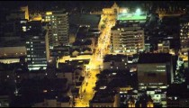 Cars turn at an intersection on a city block at night in Rio de Janeiro